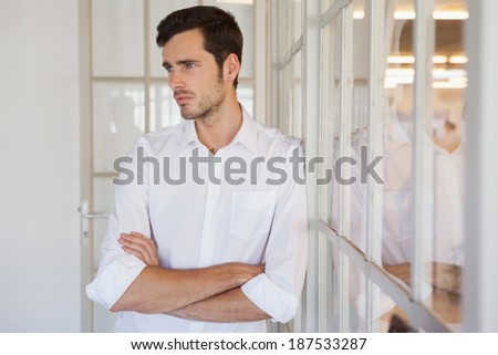 Casual upset businessman leaning against window in his office - stock photo