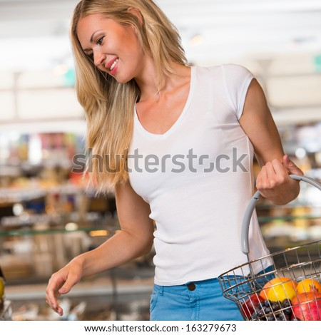 Casual woman grocery shopping at organic food section with basket - stock photo