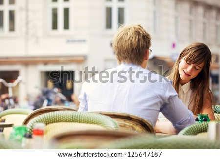 Casual woman having a conversation with her date in an open air restaurant - stock photo