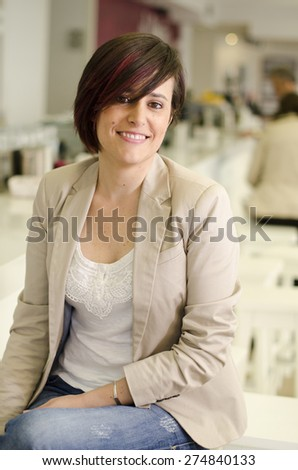 Casual woman posing and smiling in restaurant with ambient light - stock photo