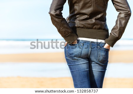 Casual woman with hands in jean pockets looking to the sea on beach. Sexy casual girl relaxing on holidays. Copy space. - stock photo