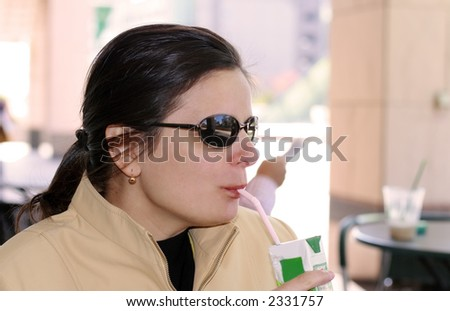 Casual woman with sunglasses drinking juice on the terrace - stock photo