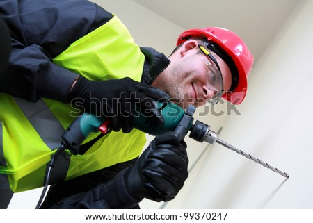 Casual worker with drill - stock photo