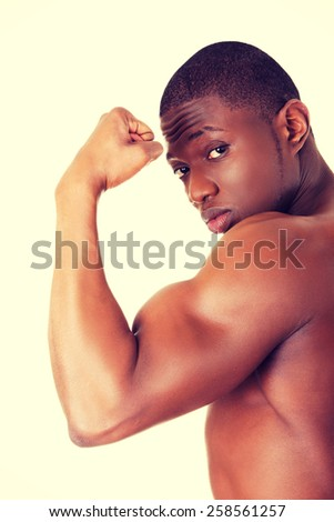 Casual young african muscular man showing his biceps. - stock photo