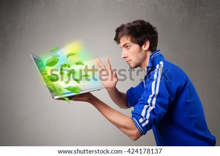 Casual young boy holding laptop with recycle and environmental symbols - stock photo