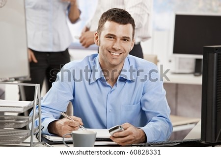 Casual young businessman working in office, sitting at desk, writing notes to personal organizer. - stock photo