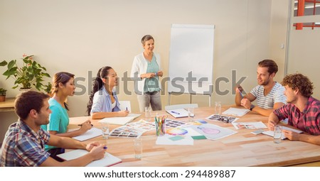 Casual young businesswoman giving a presentation to her colleagues - stock photo