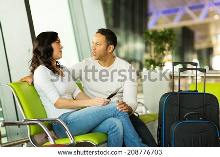 casual young couple waiting for their flight at airport - stock photo