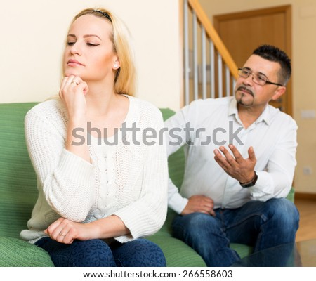 Casual young family having quarrel at house. Focus on the woman - stock photo