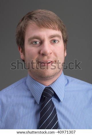Casual young handsome businessman portrait on grey background - stock photo