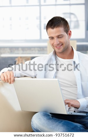 Casual young man browsing internet at home, sitting on sofa, smiling.? - stock photo