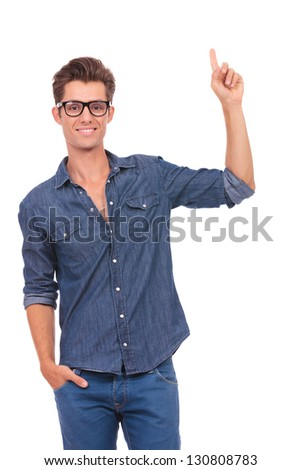 casual young man holding a hand in his pocket and pointing upwards with the other while smiling to the camera. isolated on a white background - stock photo