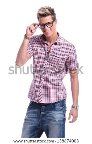 casual young man holding his hand on his eyeglasses, while smiling to the camera. on white background - stock photo