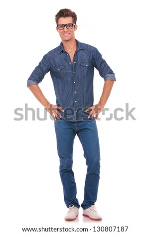casual young man holding his hands on his hips while smiling to the camera. isolated on white - stock photo
