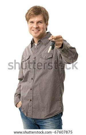 Casual young man holding ignition keys, smiling. Isolated on white.? - stock photo