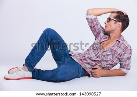 casual young man laying on the floor and putting his hand through his hair while looking away from the camera. on gray background - stock photo