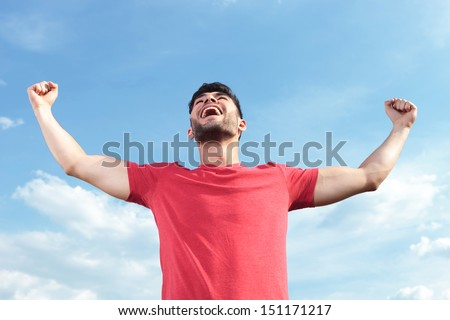 casual young man outdoor facing the sky and shouting with his fists raised - stock photo