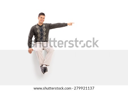 Casual young man sitting on a blank signboard, pointing with his hand and looking at the camera isolated on white background - stock photo