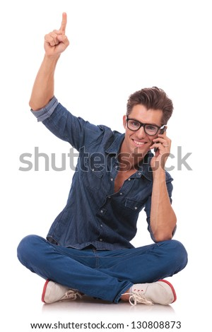 casual young man speaking on the phone and pointing upwards while smiling to the camera, from a cross legged position. isolated on white - stock photo