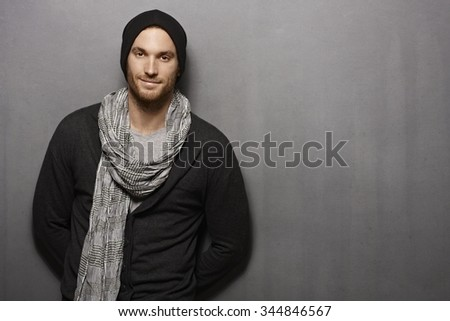 Casual young man standing against grey wall, smiling. looking at camera. - stock photo