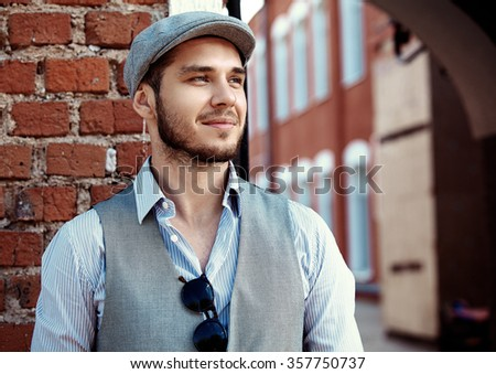 casual young man stands with his back against a brick wall - stock photo