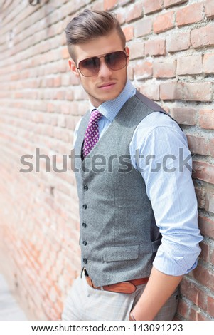 casual young man stands with his back against a brick wall with his hands in his pockets while looking away from the camera - stock photo