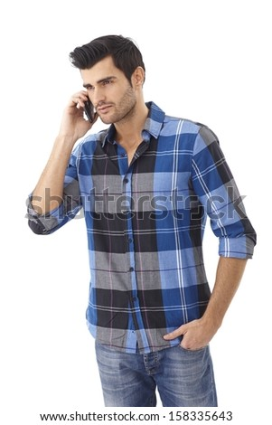 Casual young man talking on mobilephone, looking away. Isolated on white. - stock photo