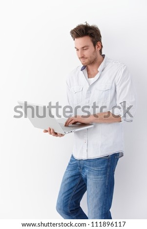Casual young man using laptop, standing by wall. - stock photo