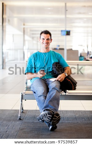 casual young man waiting for flight at airport - stock photo
