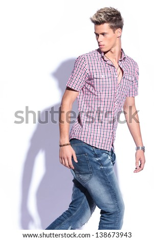 casual young man walking and looking back, away from the camera . on white background with shadow - stock photo