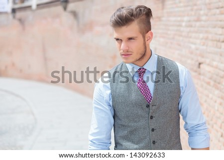 casual young man walking by a brick wall and looking away from the camera - stock photo
