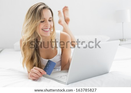 Casual young woman doing online shopping through laptop and credit card in bed - stock photo