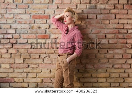 Casual young woman posing over brick wall in retro style. - stock photo