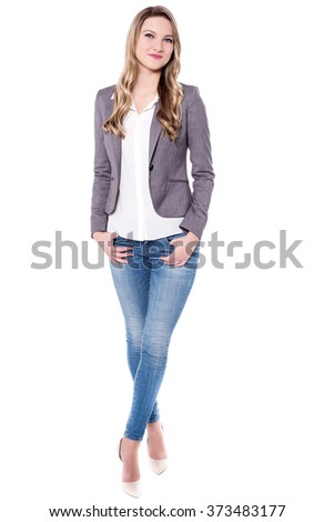 Casual young woman posing to camera with hands in pockets - stock photo