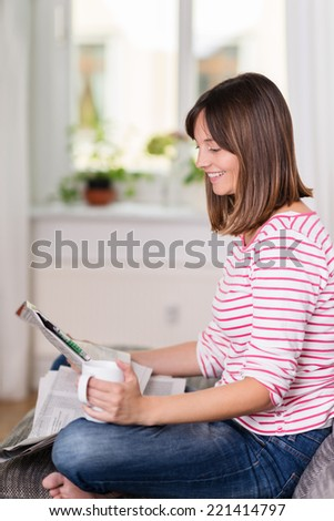 Casual young woman relaxing with a newspaper and coffee at home smiling as she reads an article of news while sitting cross-legged on a sofa - stock photo
