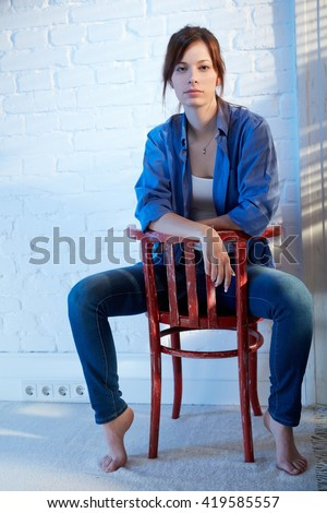 Casual young woman sitting on chair backwards, thinking. - stock photo