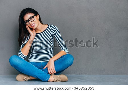 Casually beautiful. Attractive young woman touching her face and smiling while sitting on the floor and against grey background - stock photo