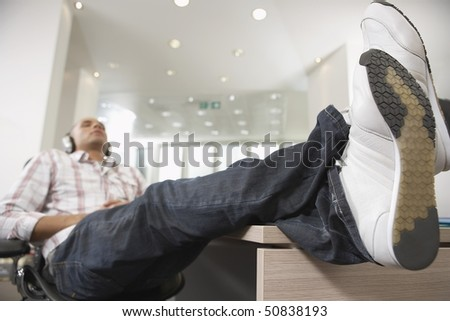 Casually dressed Businessman reclining with feet on desk,  Listening to Music With Headphones - stock photo