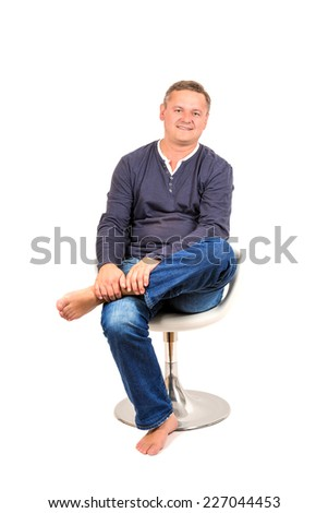 Casually dressed middle aged man smiling. Sitting on chair man shot in vertical format isolated on white. - stock photo