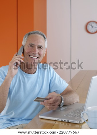 Casually dressed senior male with credit card and telephone sitting at laptop - stock photo