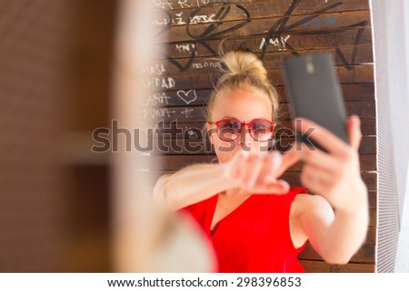 Casually dressed young cheerful lady wearing red sunglasses taking carefree selfie portrait outdoors with her android smarthphone to post it on social networks. - stock photo