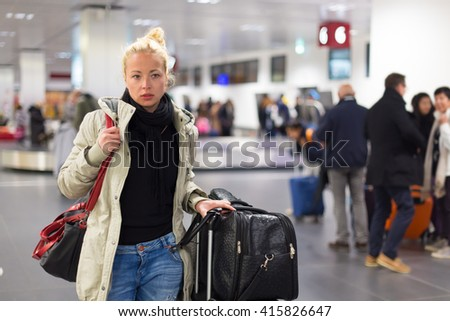 Casually dressed young female traveller walking in airport terminal hall with collected laggage after flight arrival . Blured background. Can also be used as railway, metro, bus station. - stock photo