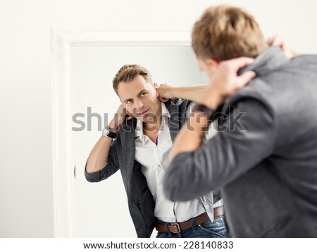 Casually dressed young handsome man in front of mirror - stock photo