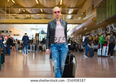 Casually dressed young stylish female traveller walking the airport terminal hall   dragging suitcase and a handbag behind her. Blurred background. Can also be used as railway, metro, bus station. - stock photo