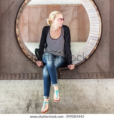 Casually dressed young urban lady wearing red sunglasses sitting on contemporary circular wooden bench in city park. Square composition. - stock photo