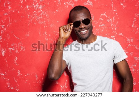 Casually handsome. Cheerful young African man adjusting his sunglasses and smiling while standing against red background - stock photo