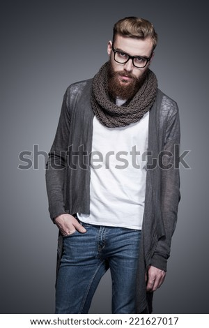 Casually handsome. Handsome young bearded man in eyeglasses holding one hand in pocket and looking at camera while standing against grey background - stock photo
