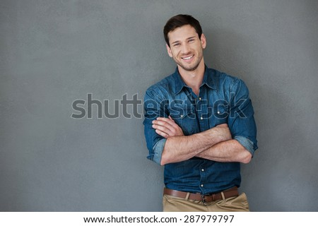 Casually handsome. Happy young man keeping arms crossed and smiling at camera while standing against grey background - stock photo