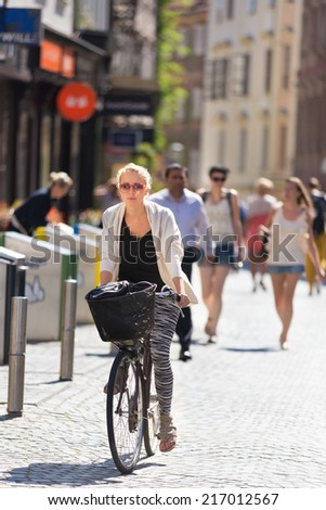 Casualy dressed lady riding bicycle trough medieval city center of Ljubljana, capital of Slovenia. Environmentally friendly and healthy way of urban transportation. - stock photo