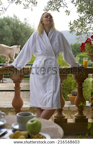 Cat next to woman in bathrobe leaning against patio railing with eyes closed - stock photo